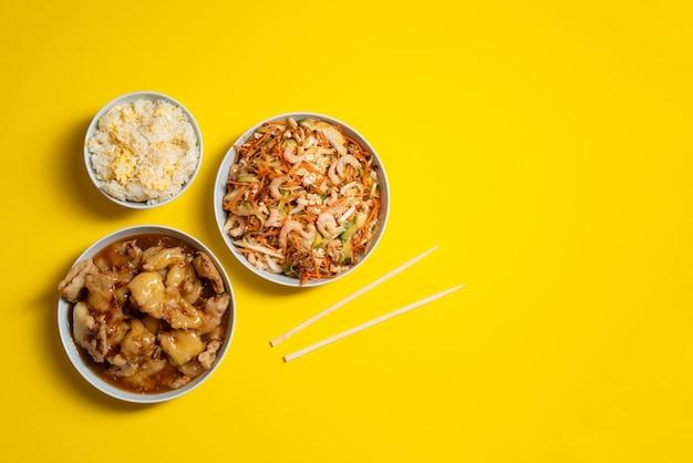 Яркая тарелка салата из креветок, хрустящего цыпленка, миска риса с яйцом и палочками для еды на желтом фоне. еда на вынос.