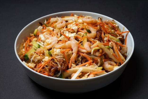 Яркая тарелка салата из креветок. традиционный салат из креветок с овощами. красочная миска с морепродуктами на черном фоне.