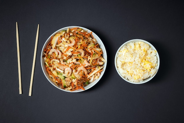 Vibrant plate of shrimp salad, bowl of rice with egg and chopsticks on black