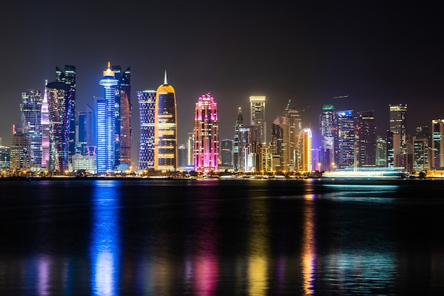 Vibrant skyline of doha at night as seen from the opposite side of the capital city bay at night.