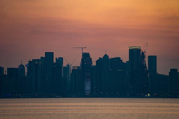 Яркий горизонт дохи на драматическом закате, вид с противоположной стороны столичного залива.