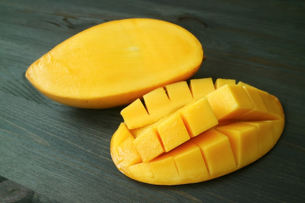 Vibrant yellow fresh ripe thai nam dok mai mango cut in half on dark brown wooden table