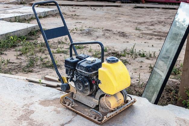 Вибротрамбовка с виброплитой на строительной площадке. уплотнение почвы перед укладкой тротуарной плитки. крупный план.