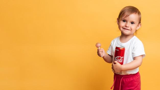 비츄가. 러시아. 2020년 2월 27일: 행복한 소녀가 손에 코카콜라 캔과 막대 사탕을 들고 서 있습니다. 이 제품에는 설탕이 많이 포함되어 있어 어린이에게 해롭습니다. 텍스트를 위한 장소