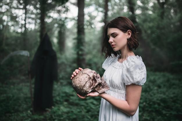 Victim holds human skull, death on background