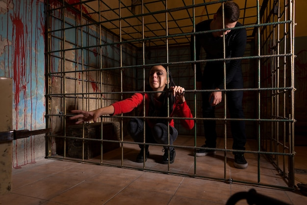 Victims imprisoned in a metal cage with a blood splattered wall behind them, girl pulling her hand through the bars and trying to get out