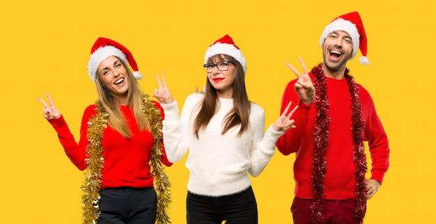 人々のグループブロンドの女性は笑顔とvictoを見せているクリスマス休日のために身に着けている