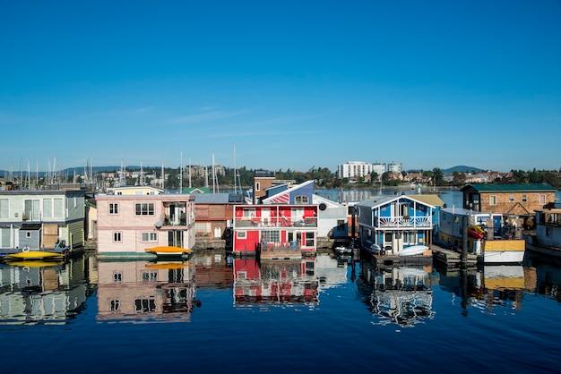 Виктория, британская колумбия, канада. рыбацкая пристань. разноцветные плавучие дома.