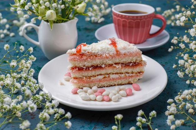 Victoria sponge cake slices with a cup of coffee on light