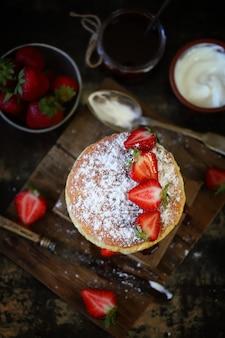 いちごと白いクリームが付いているビクトリアスポンジケーキ。