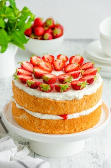 딸기 잼, 휘핑 크림 및 신선한 딸기를 곁들인 빅토리아 스폰지 케이크