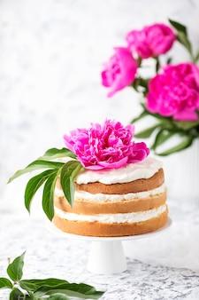 Victoria sponge cake with white cheese cream decorated pink peony