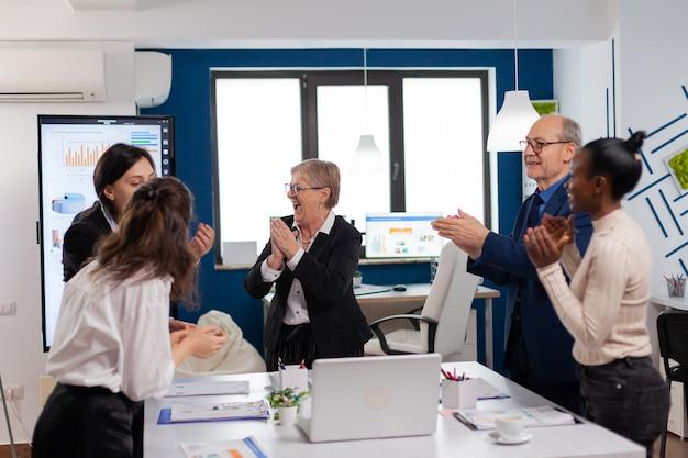 会議室で一緒に拍手するビジネスマンの勝利の大喜びの多様なチーム