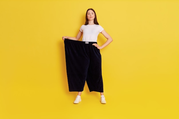 Victorious woman holding her too big pants and looking directly at camera, being proud of her result, standing isolated over yellow wall, keeps hand on hip and shows her achieving goal.