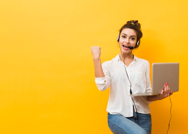 Victorious woman wearing headset and holding laptop