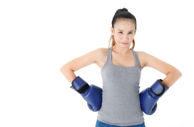 白い背景の勝利を祝っている間、手を上げて幸せそうに笑っている青いボクシンググローブの勝利の若いアジアの女性の戦闘機