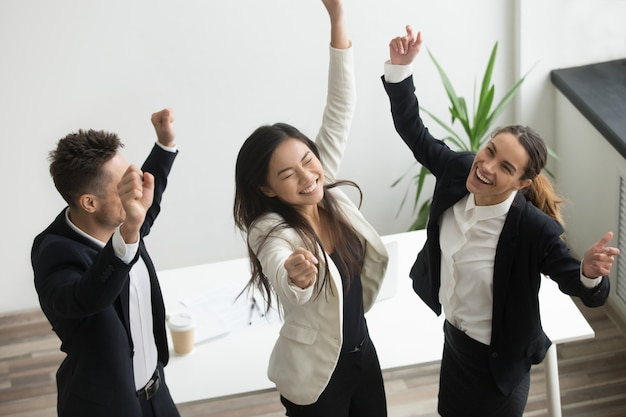 Victory dance concept, excited diverse coworkers celebrating business success