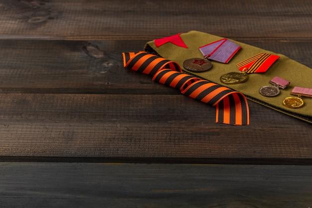 Фон победы - 9 мая 1945 года. георгиевская ленточка, фронтовые письма, военная гарнизонная шапка и ордена на деревянном фоне. вид сверху, скопируйте пространство для текста