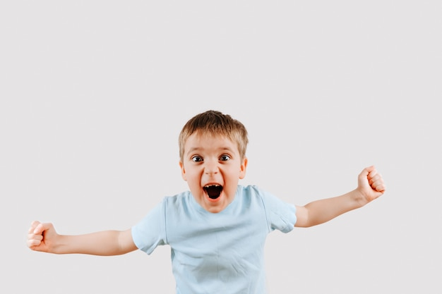 Victory screaming kid. portrait of emotional caucasian little boy shouting with his hands up