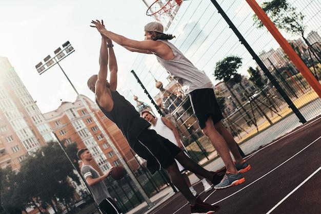 勝利!屋外で友達とバスケットボールをしながら勝利の象徴でお互いにハイタッチを与えるスポーツウェアの2人の若い男性
