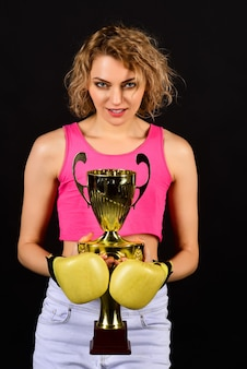Victory, winner and success concept - beautiful woman in sportswear with boxing gloves holding gold winner trophy. excited fighter boxer girl celebrates victory holds champion golden cup on her hands.