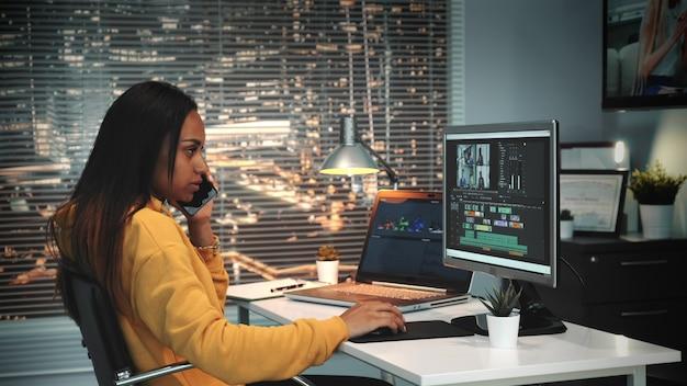 ビデオとサウンドエディターの女性が電話で話し、ビデオをマウント