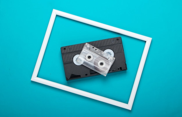 Video and audio cassette on blue surface with white frame