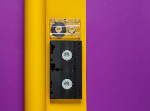 Video and audio cassette on yellow purple paper