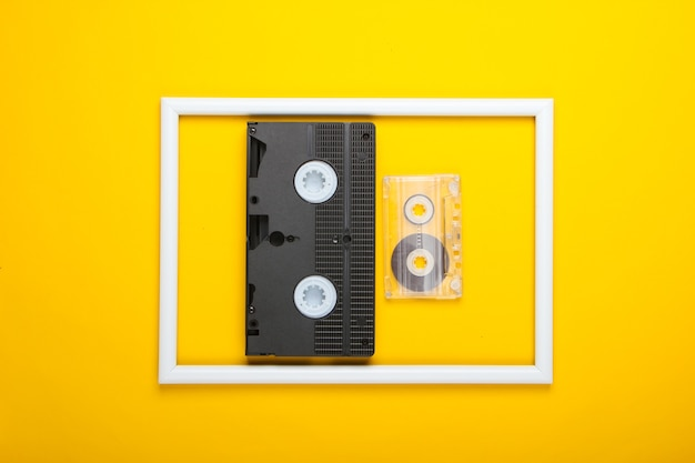 Video and audio cassette on yellow surface with white frame
