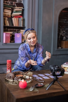 Video blog. nice young woman speaking about magical items while having her own video blog