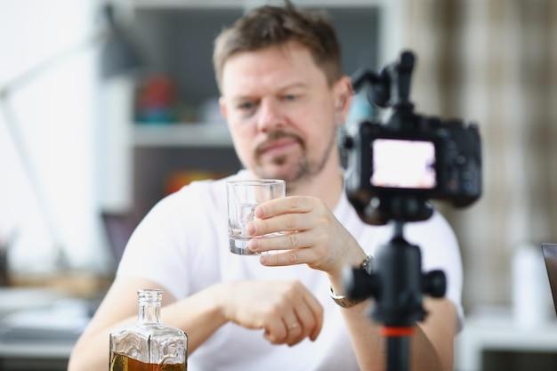 ビデオブロガーはカメラの前で一人でアルコールを飲む