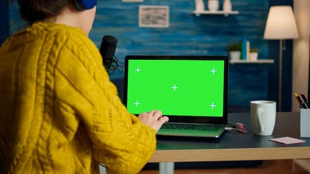 비디오 블로거는 방송 중에 녹색 화면이 표시된 노트북에서 이메일을 읽습니다. 크리에이티브 온라인 쇼 온에어 프로덕션 인터넷 방송 호스트 크로마 키 노트북을 사용하여 라이브 콘텐츠 스트리밍