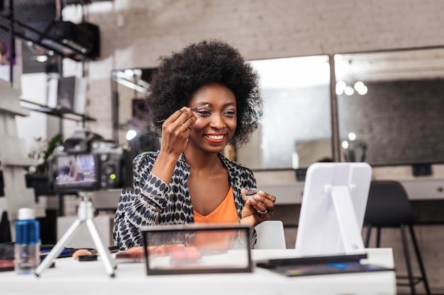 ビデオブロガー。眉を修正する方法を示すオレンジ色のトップを着て笑顔の浅黒い肌の女性