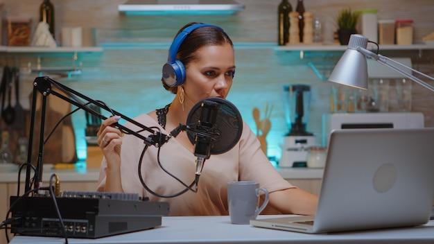 비디오 블로거는 랩톱에 입력하고 전문 마이크를 사용하여 팟캐스트용 음성을 녹음합니다. 창작 온라인 쇼 온에어 프로덕션 인터넷 방송 쇼 호스트 스트리밍 라이브 콘텐츠, 녹음 디지