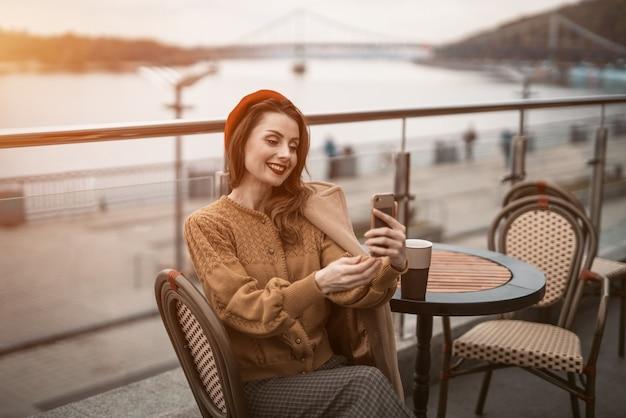 Видеозвонок красивая молодая женщина с помощью своего смартфона за чашкой кофе. французская женщина