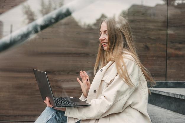 Концепция видеозвонка. молодая кавказская блондинка студентка сидит на лестнице, улыбаясь и махая рукой на экране монитора