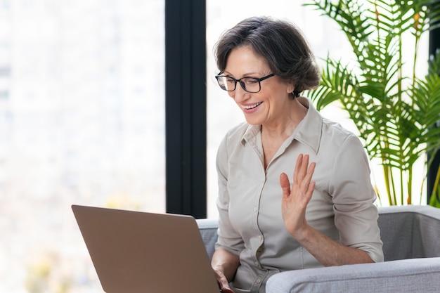 화상 통화, 원격 작업 개념입니다. 사무실이나 집에서 안락의자에 앉아 인터넷을 통해 온라인 통신을 위해 랩톱 컴퓨터를 사용하는 아름다운 백인 여성