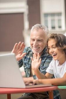 ビデオ通話。ノートパソコンと一緒に座ってビデオ通話をしている息子とお父さん