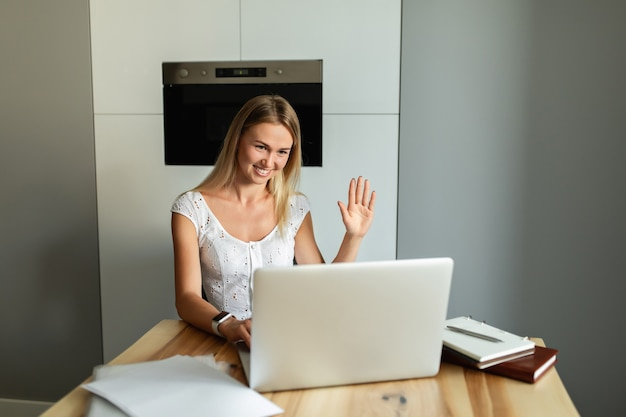 Video call, video conference with other people on laptop indoors. online learning and work. woman with laptop computer working at home office