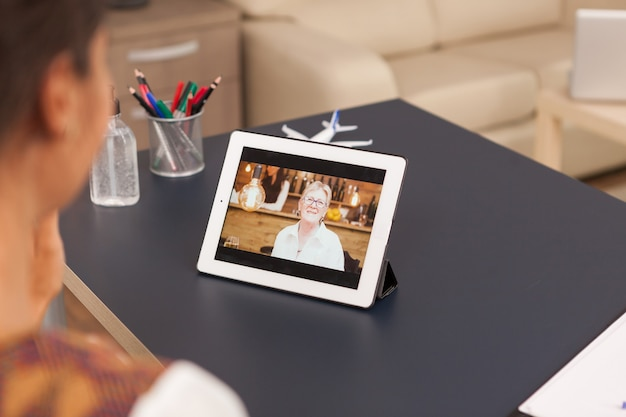 Video call with parent on tablet computer from home office.