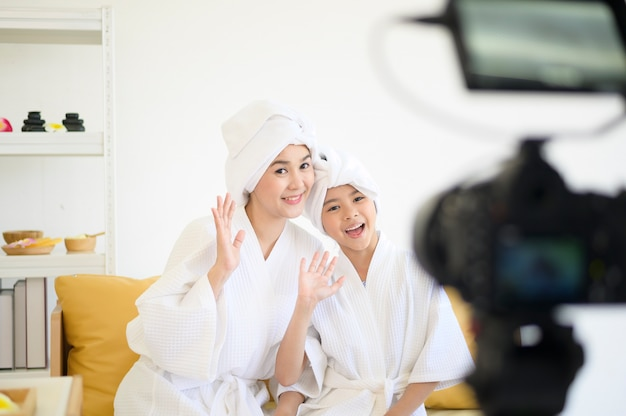 A video camera filming happy mom and daughter in white bathrobe