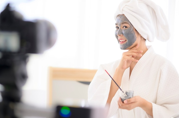 Video camera filming woman in white bathrobe applying a face mask for movie, behind the scenes of shoot