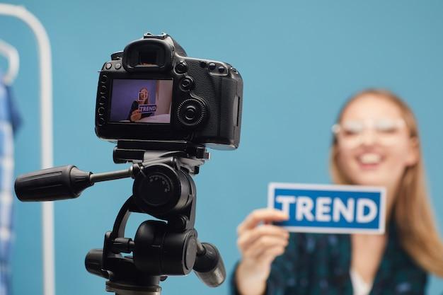 Видеокамера на штативе с женщиной, снимающей контент для своего блога