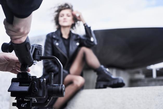 Оператор видеокамеры, работающий с девушкой фотомодели на открытом воздухе
