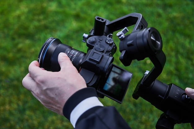 Video camera operator working with professional equipment close up