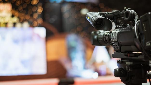 会議室でバックグラウンドで働いている人々とのライブビデオストリーミングを撮影するビデオカメラ。