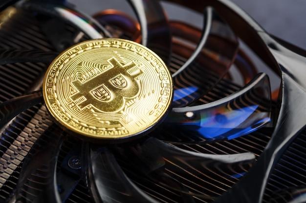 クーラーのクローズアップに金貨ビットコインが付いたビデオカード