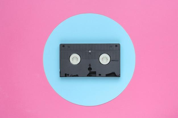 파란색 파스텔 원이 있는 분홍색 배경의 비디오 카세트. 최소한의 복고풍 개념입니다. 80년대. 평면도