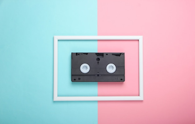 Video cassette on pink blue pastel surface with white frame