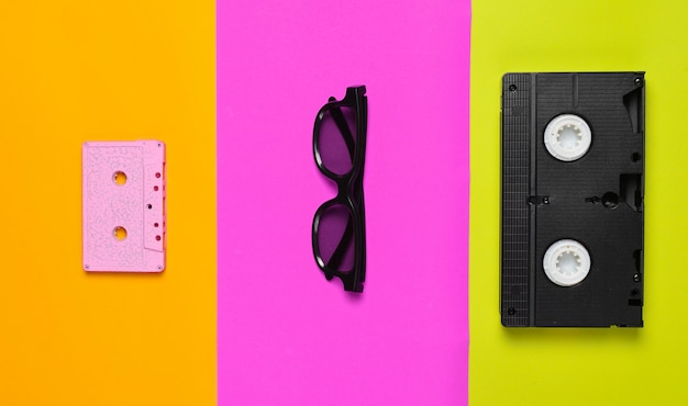 Video cassette, sunglasses, audio cassette on a multi-colored paper.